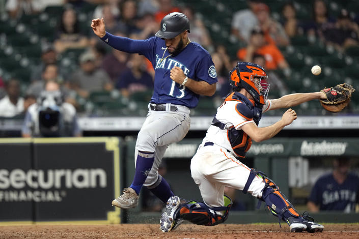 Seattle Mariners' Abraham Toro (13) scores as Houston Astros catcher Garrett Stubbs reaches for the ball during the ninth inning of a baseball game Tuesday, Sept. 7, 2021, in Houston. (AP Photo/David J. Phillip)