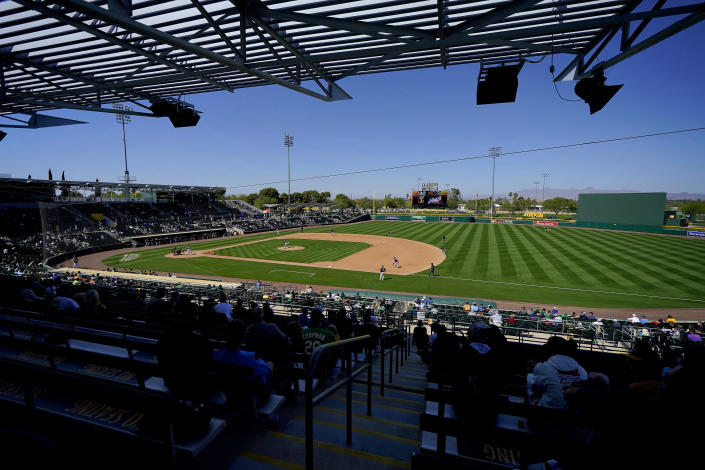 The Oakland Athletics and the Milwaukee Brewers compete during the third inning of a spring training baseball game, Wednesday, March 10, 2021, in Mesa, Ariz. (AP Photo/Matt York)