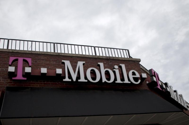 People pass by a T-Mobile store in the Brooklyn borough of New York