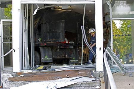 A Baltimore county firefighter officer walks out the broken door at the entrance of the WMAR-TV station in Towson