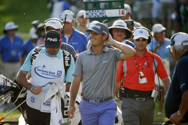 Billy Horschel, center, walks on to the 18th green during the final round of the Deutsche Bank Championship golf tournament in Norton, Mass., Monday, Sept. 1, 2014. (AP Photo/Michael Dwyer)