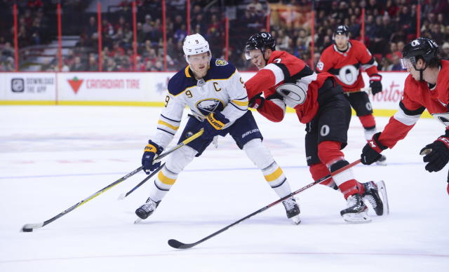 Buffalo Sabres center Jack Eichel (9) moves the puck around Ottawa Senators left wing Brady Tkachuk (7) during the first period of an NHL hockey game Monday, Dec. 23, 2019, in Ottawa, Ontario. (Sean Kilpatrick/The Canadian Press via AP)