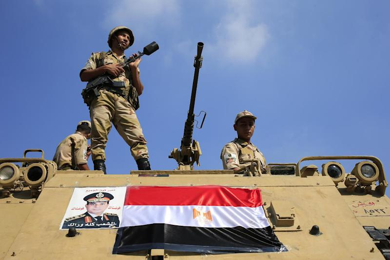 Egyptian soldiers stand guard atop an armored personnel vehicle on a bridge that leads to Tahrir Square in Cairo, Egypt, Friday, July 26, 2013. Political allies of Egypt's military lined up behind its call for huge rallies Friday to show support for the country's top general, pushing toward a collision with Islamist opponents demanding the return of the nation's ousted president, Mohammed Morsi. (AP Photo/Hassan Ammar)