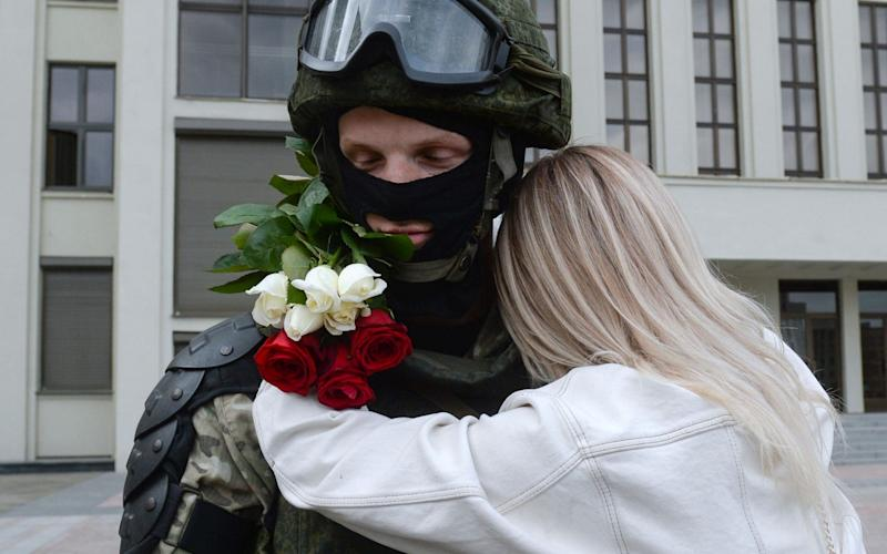 A woman embraces a member of the Belarusian interior ministry troops in Minsk during the rally against police brutality and the election results - Shutterstock