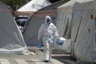 A health worker wearing protective suits walks in between tents at a parking lot that has been converted into an extension of the Gat Andres Bonifacio Memorial Medical Center in Manila, Philippines on Monday, Aug. 3, 2020. Philippine President Rodrigo Duterte is reimposing a moderate lockdown in the capital and outlying provinces after medical groups appealed for the move as coronavirus infections surge alarmingly. (AP Photo/Aaron Favila)