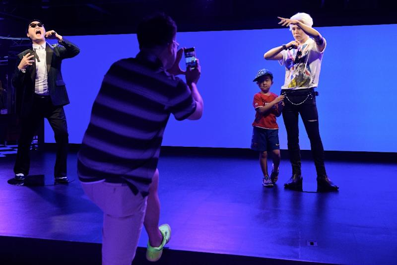 A child poses for a photo with a waxwork model of Kpop star G-Dragon on the opening day of the first Asian outpost of France's famous waxwork museum, Musee Grevin, in Seoul on July 30, 2015 (AFP Photo/Ed Jones)