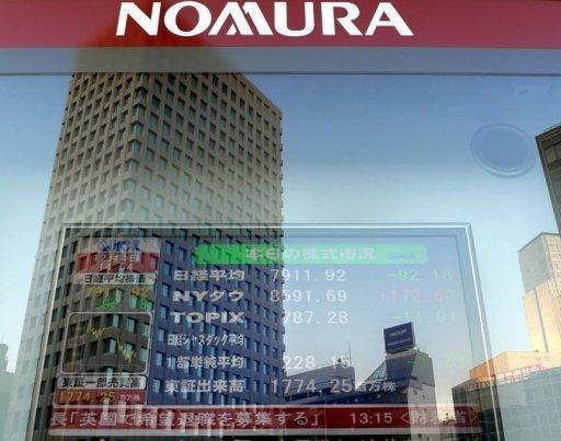 File photo of an electronic share price board in front of a Nomura Securities' branch in Tokyo. Top Japanese brokerage Nomura will cut its chief executive's pay as a penalty for an embarrassing string of insider trading scandals, reports said Friday, as regulators ramp up a probe