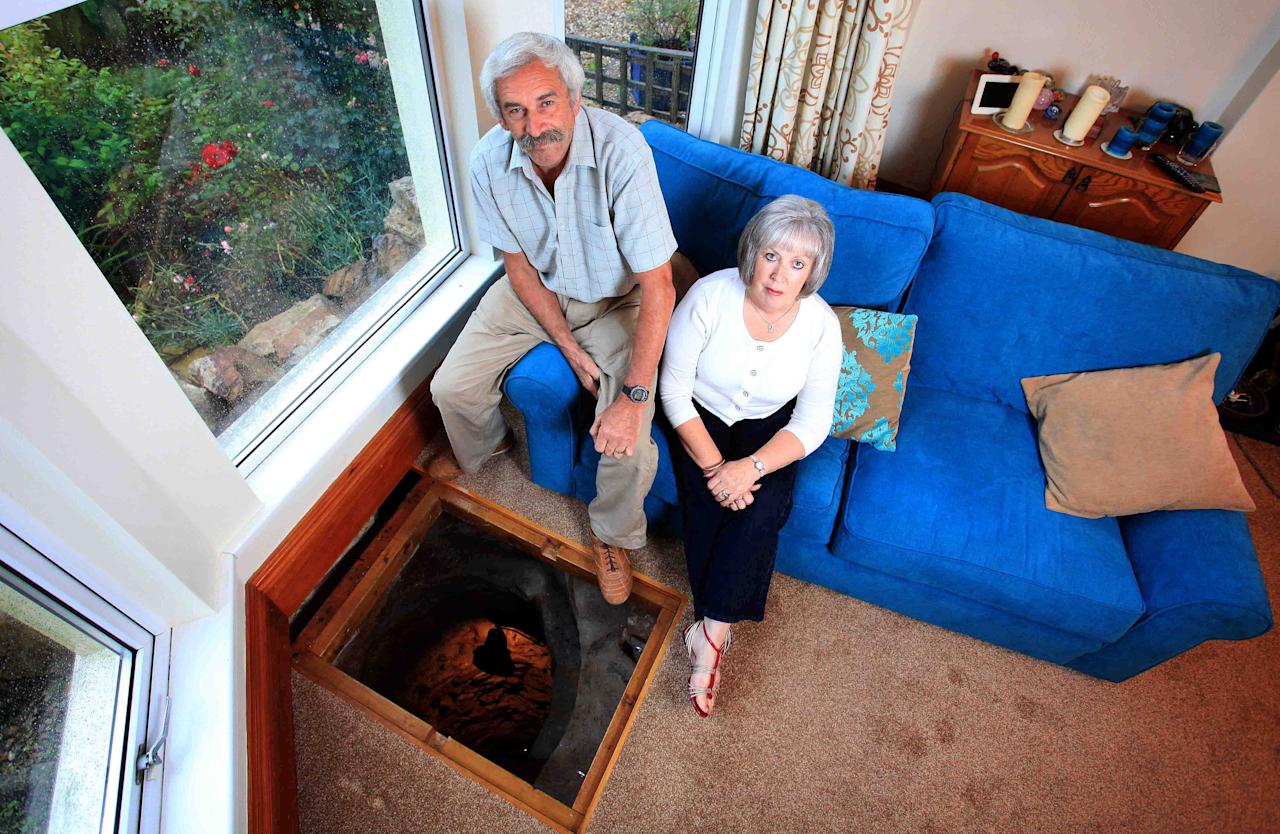 Colin Steer, and wife Vanessa, 61, who have lived in their Victorian home for 24 years first discovered a slight indentation in their living room floor after they moved in. Colin recently decided to investigate further and after a little digging discovered a 33ft well. No pot of gold down there but he did find a sword. Picture: SWNS