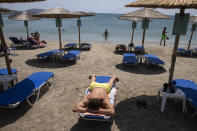 A man sunbathes at a beach of Lagonissi village, a few miles southwest of Athens, on Thursday, July 29, 2021. One of the most severe heat waves recorded since 1980s scorched southeast Europe on Thursday, sending residents flocking to the coast, public fountains and air-conditioned locations to find some relief, with temperatures rose above 40 C (104 F) in parts of Greece and across much of the region. (AP Photo/Yorgos Karahalis)