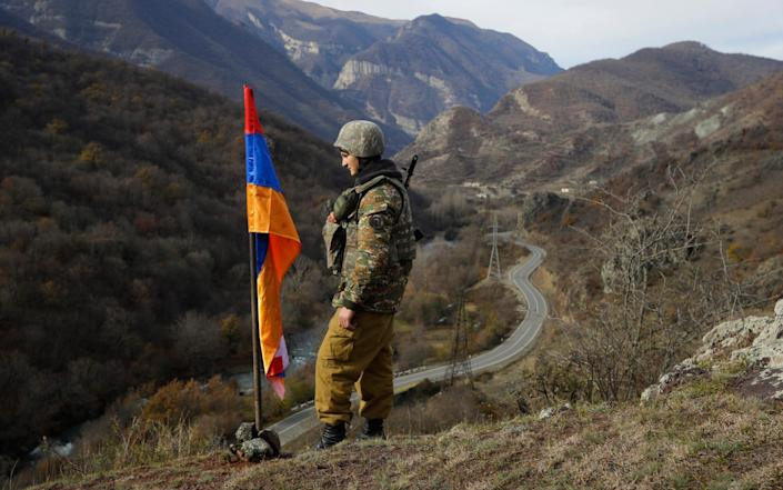 An ethnic Armenian soldier stands guard in Nagorno-Karabakh at a new border with Kalbajar district - Sergei Grits /AP