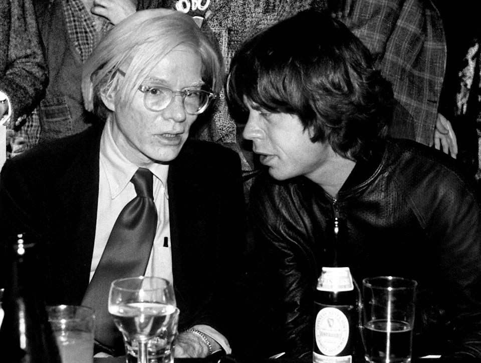 <p>Andy Warhol talks to Mick Jagger from The Rolling Stones at a party in New York in 1977.</p>