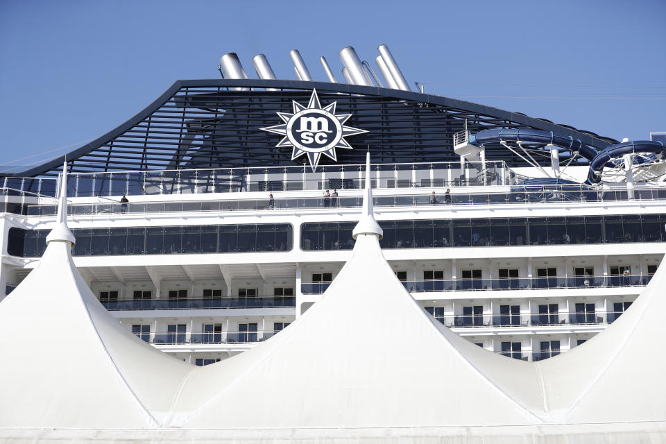 Cruise ship passengers aboard the MSC Divina look off the balconies as they wait to shove off at PortMiami, Friday, Feb. 28, 2020, in Miami. The spread of a new coronavirus from China is disrupting the cruise industry in the midst of its busiest season for bookings. (AP Photo/Wilfredo Lee)