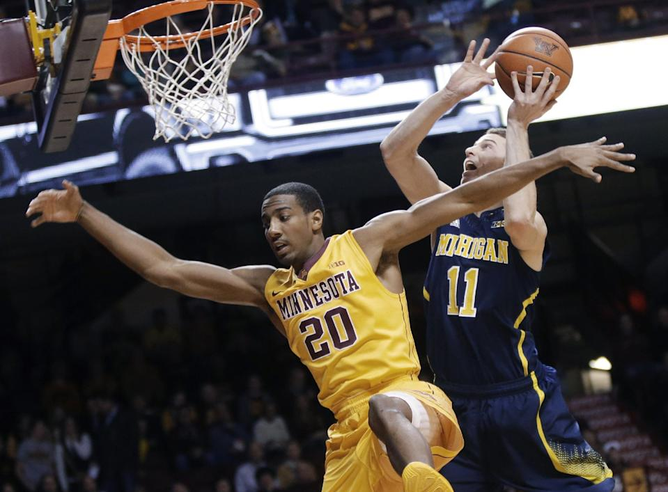 Michigan's Nik Stauskas, right, attempts a shot and is fouled by Minnesota's Austin Hollins during the first half of an NCAA college basketball game Thursday, Jan. 2, 2014, in Minneapolis. (AP Photo/Jim Mone)