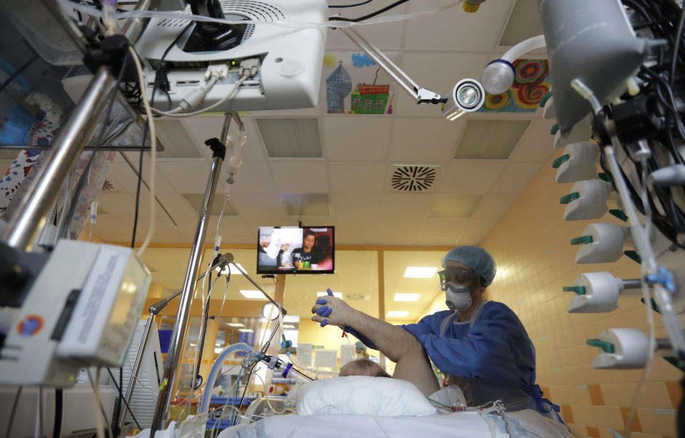 FILE - In this April 7, 2020 file photo a healthcare worker attends to a COVID-19 patient in an intensive care unit (ICU) at the General University Hospital in Prague, Czech Republic. (AP Photo/Petr David Josek, File)