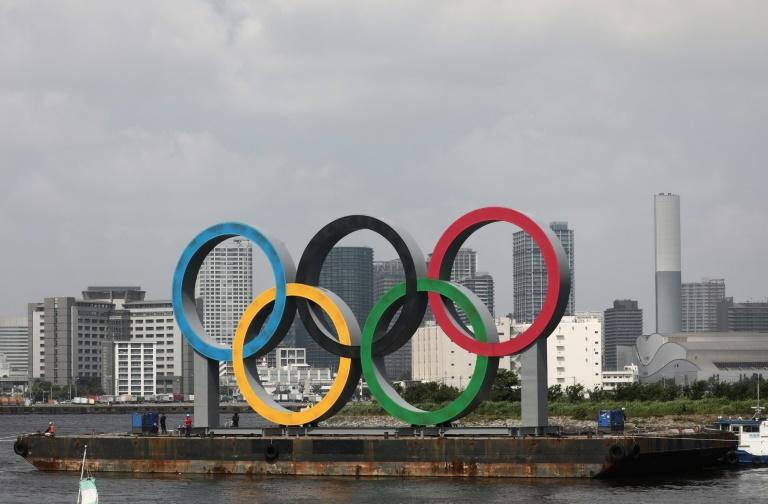 Giant Olympic rings in Tokyo towed away for maintenance