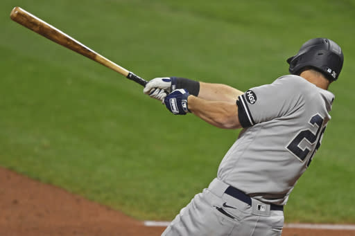 New York Yankees' DJ LeMahieu (26) hits a RBI single in the fourth inning of Game 1 of an American League wild-card baseball series against the Cleveland Indians, Tuesday, Sept. 29, 2020, in Cleveland. (AP Photo/David Dermer)