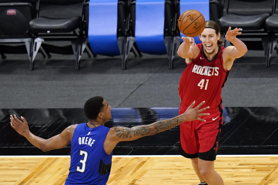 Houston Rockets forward Kelly Olynyk (41) passes the ball over Orlando Magic forward Chuma Okeke (3) during the second half of an NBA basketball game, Sunday, April 18, 2021, in Orlando, Fla. (AP Photo/John Raoux)