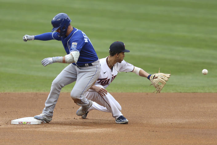 Kansas City Royals' Whit Merrifield, left, makes it safely to second base against Minnesota Twins' Andrelton Simmons, right, after hitting a ground ball to right fielder Alex Kirilloff during the first inning of a baseball game Sunday, May 30, 2021, in Minneapolis. (AP Photo/Stacy Bengs)