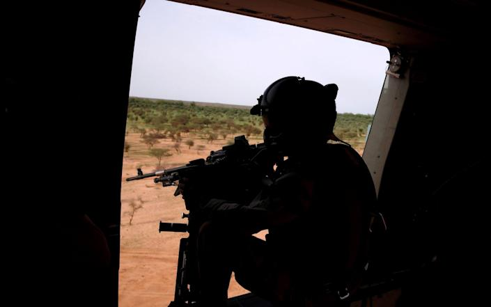 A French soldier mans a machine gun in the door of a NH 90 Caiman military helicopter during Operation Barkhane over Ndaki - Benoit Tessier/Reuters