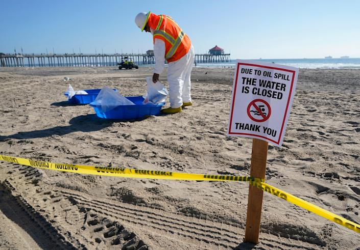 A member of a cleanup crew changes his protective clothing after looking for oil on Huntington Beach, Calif. More than 125,000 gallons of oil spilled from a pipeline about four miles offshore of Southern California's coast. The spill left a sheen over miles of ocean along the shoreline at Huntington Beach.