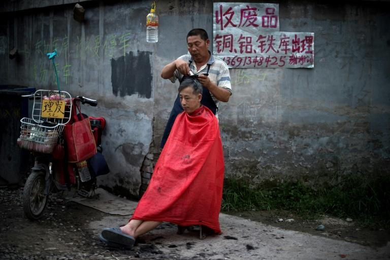 A man gets a haircut on a street in a migrant village on the outskirts of Beijing