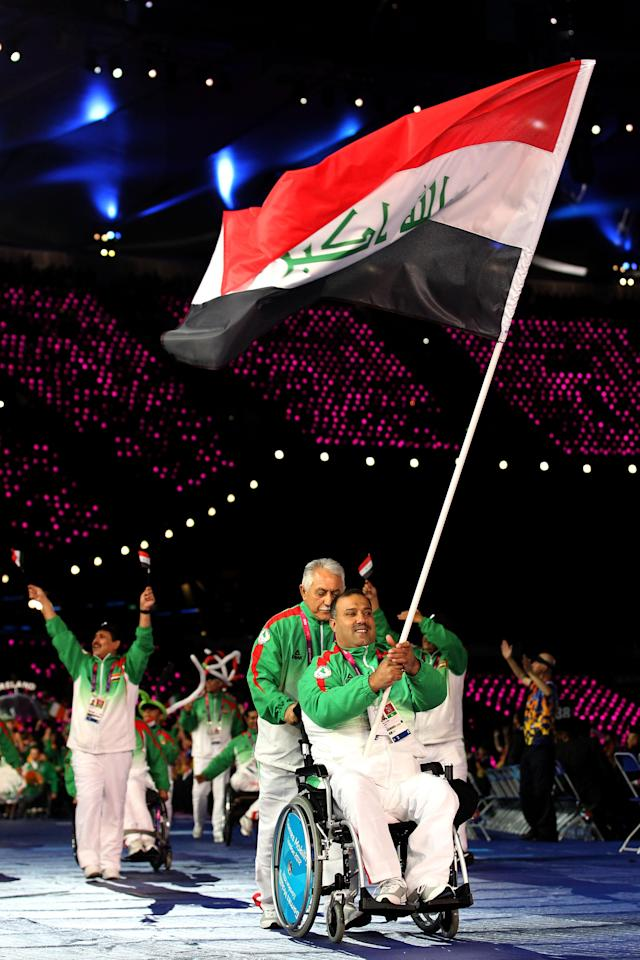 LONDON, ENGLAND - AUGUST 29: Powerlifter Faris Al-Ajeeli of Iraq carries the flag during the Opening Ceremony of the London 2012 Paralympics at the Olympic Stadium on August 29, 2012 in London, England. (Photo by Dan Kitwood/Getty Images)