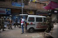 Indian paramilitary force soldiers patrol as an ambulance stationed at the area which witnessed Tuesday's violence in New Delhi, India, Wednesday, Feb. 26, 2020. At least 20 people were killed in three days of clashes in New Delhi, with the death toll expected to rise as hospitals were overflowed with dozens of injured people, authorities said Wednesday. The clashes between Hindu mobs and Muslims protesting a contentious new citizenship law that fast-tracks naturalization for foreign-born religious minorities of all major faiths in South Asia except Islam escalated Tuesday. (AP Photo/Rajesh Kumar Singh)