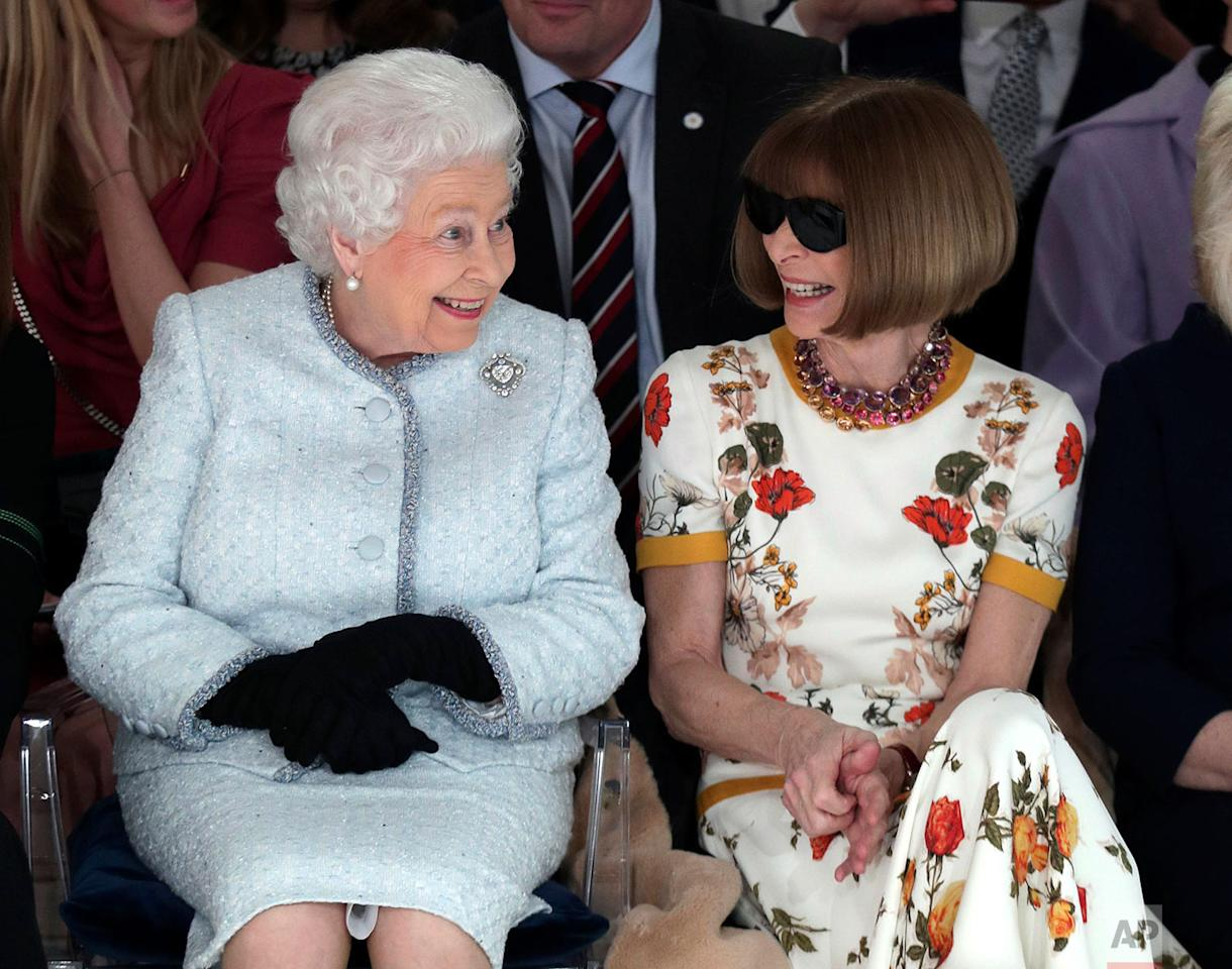 <p>Britain's Queen Elizabeth sits next to Vogue editor Anna Wintour as they view Richard Quinn's runway show before presenting him with the inaugural Queen Elizabeth II Award for British Design, as she visits London Fashion Week's BFC Show Space in central London. (Yui Mok/Pool photo via AP) </p>