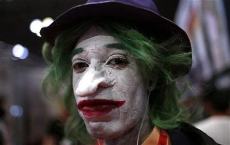 A fan dressed as the Joker from the Batman comic and movie series poses for a photograph at New York's Comic-Con convention