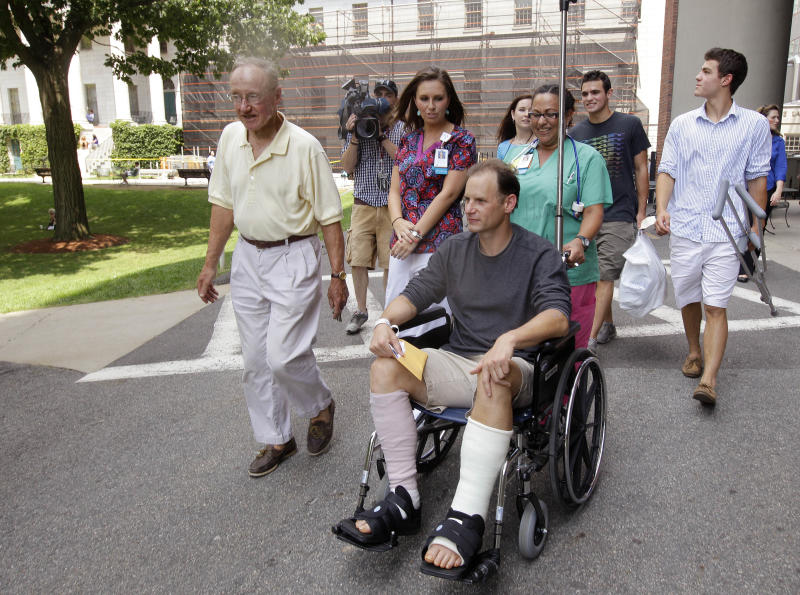 Christopher Myers, of Denver, is wheeled out of Massachusetts General Hospital with family members and hospital staff upon discharge after receiving treatment as the result of a shark attack in Boston, Friday, Aug. 3, 2012. Myers was bitten off Ballston Beach in Truro on Monday. (AP Photo/Stephan Savoia)