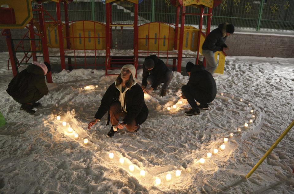 People make a heart with candles in support of jailed opposition leader Alexei Navalny and his wife Yulia Navalnaya, in the Siberian city of Omsk, Russia, Sunday, Feb. 14, 2021. When the team of jailed Russia opposition leader Alexei Navalny announced a protest in a new format, urging people to come out to their residential courtyards on Sunday and shine their cellphone flashlights, many responded with jokes and skepticism. After two weekends of nationwide demonstrations, the new protest format looked to some like a retreat. But not to Russian authorities, who moved vigorously to extinguish the illuminated protests planned for Sunday. (AP Photo)