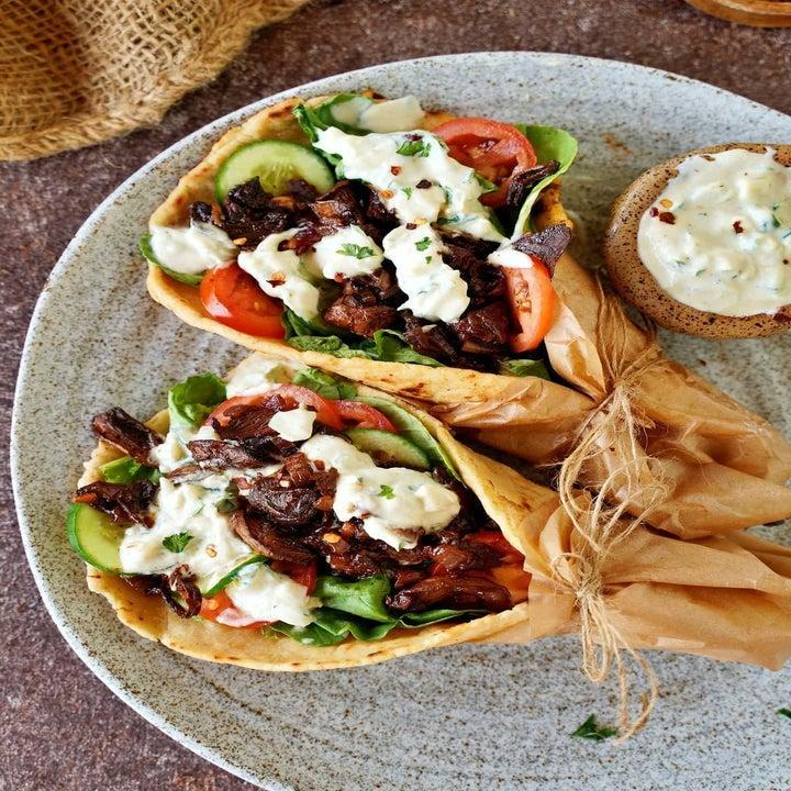 Two gyros with mushrooms, cucumber, tomatoes, and other ingredients on a plate with sauce