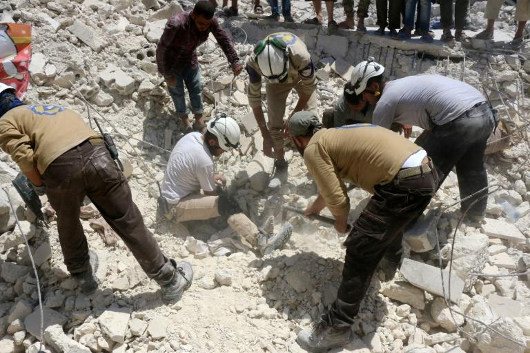 Syrian civil defence workers look for survivors under the rubble of a collapsed building following reported air strikes in a rebel-controlled neighbourhood of Aleppo