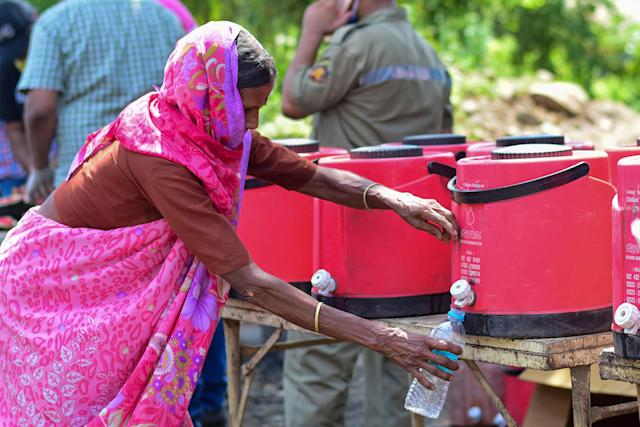 MUMBAI, MAHARASHTRA, INDIA - 2020/05/13: A woman fills her water bottle as they wait to board vehicles during the lockdown. Due to lockdown situation, most migrants are stuck in Mumbai, some walk and others arrange their own trucks and buses to their home towns, while the police say that the buses are available by the government. (Photo by Ratika More/SOPA Images/LightRocket via Getty Images)