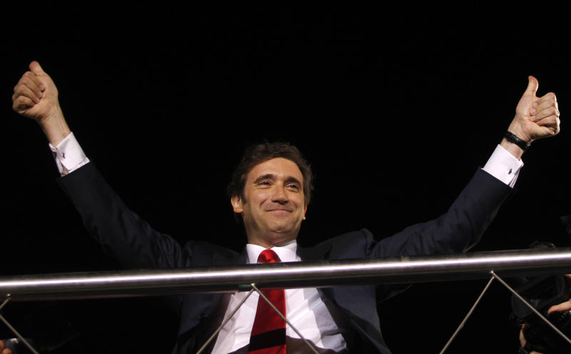 Pedro Passos Coelho, leader of the center-right Social Democratic Party, PSD, gestures to supporters from the top of an open deck bus in Lisbon after his party won Portugal's general elections Sunday, June 5 2011. (AP Photo/Francisco Seco)