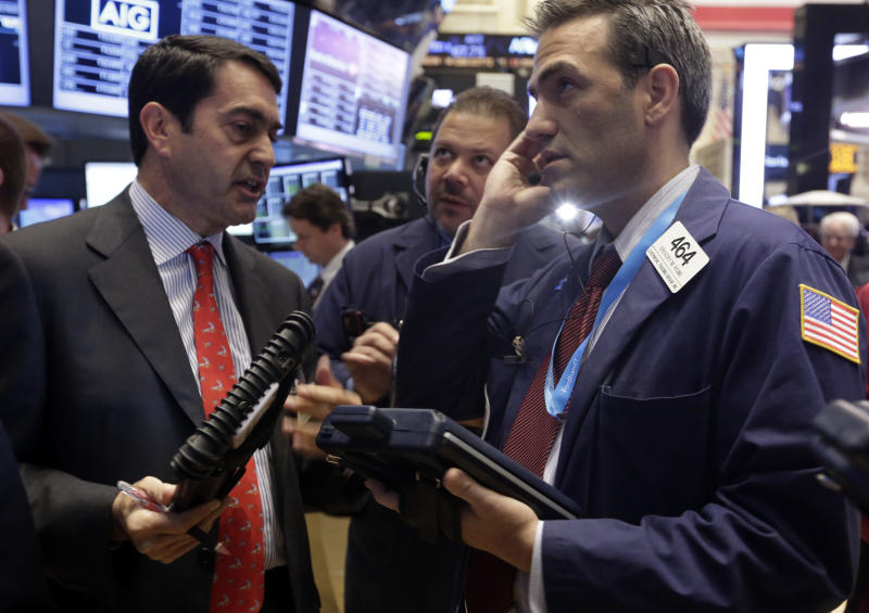 Traders Mark Muller, John Santiago and Gregory Rowe, left to right, work on the floor of the New York Stock Exchange Wednesday, Sept. 18, 2013. Stocks were little changed in early trading Wednesday as investors wait to hear from the Federal Reserve on the fate of the central bank's bond-buying program. (AP Photo/Richard Drew)
