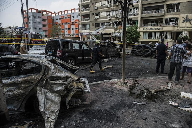 An Egyptian fireman and civilians look at the site of a bomb attack that targeted the convoy of Egyptian state prosecutor, Hisham Barakat, who died hours after the explosion in Cairo on June 29, 2015