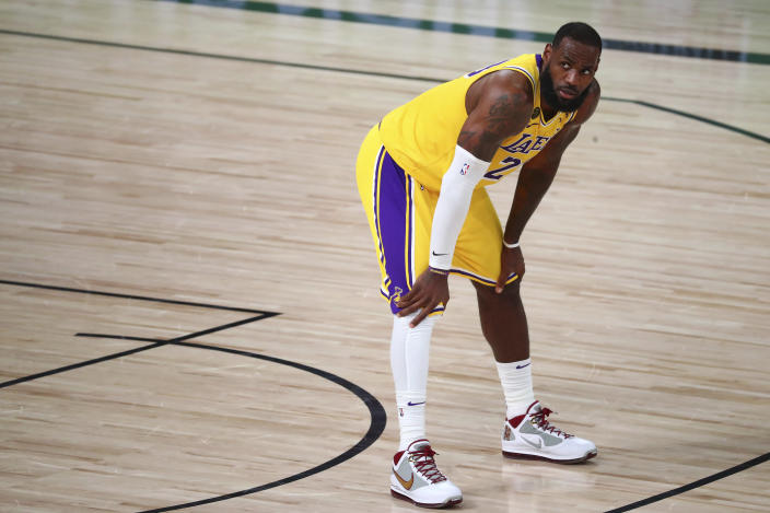 LeBron James on the court in a yellow uniform looks across.