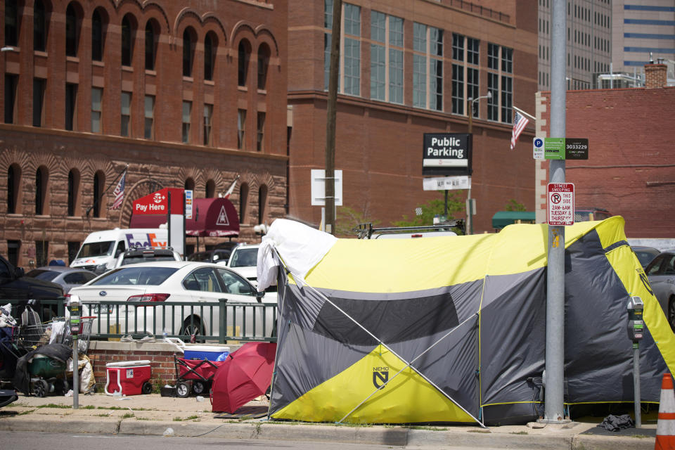 A tent put up by homeless individuals sits on a sidewalk Thursday, July 8, 2021, one block east of the Colorado Convention Center, the site of a major League Baseball promotion to mark the playing of the All Star Game in Denver. (AP Photo/David Zalubowski)