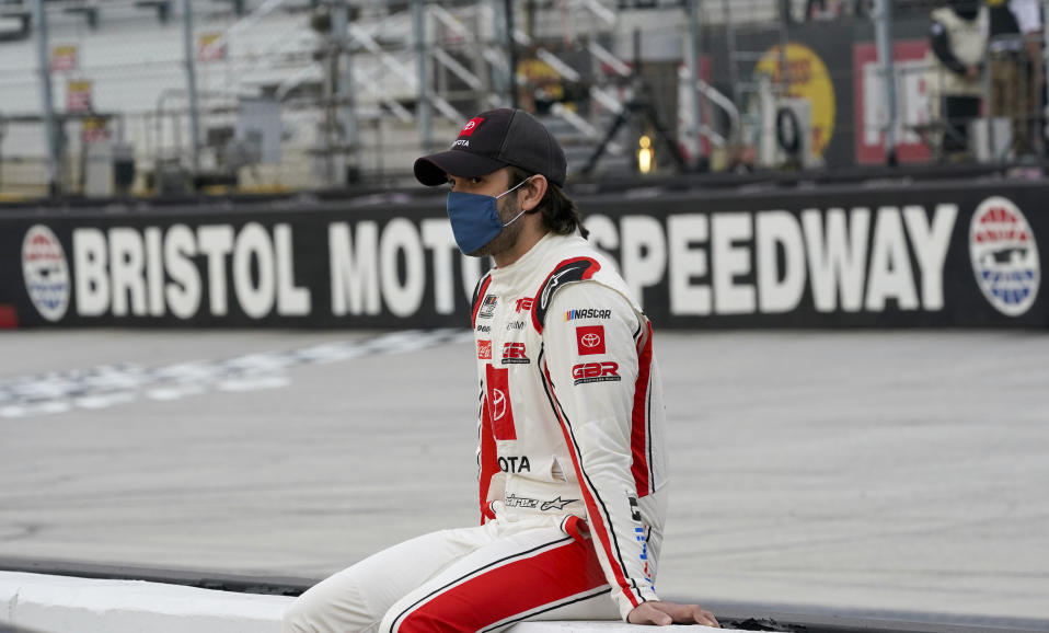 Daniel Suarez sits on a wall along pit row as he waits for driver introductions for the NASCAR Cup Series auto race Saturday, Sept. 19, 2020, in Bristol, Tenn. (AP Photo/Steve Helber)