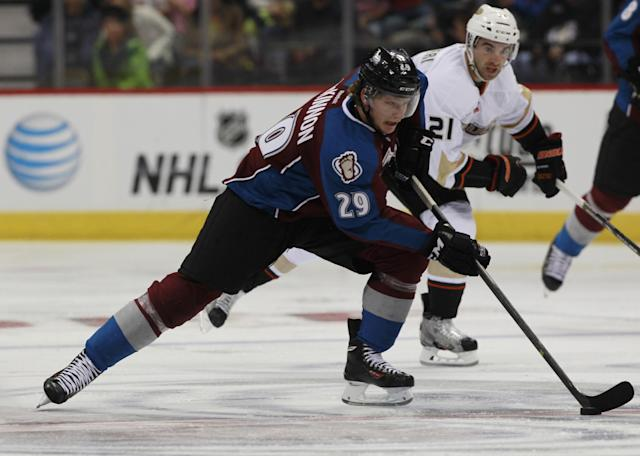 Colorado Avalanche rookie center Nathan MacKinnon, front, breaks down the ice with the puck and Anaheim Ducks right wing Kyle Palmieri in pursuit in the third period of the Avalanche's 6-1 victory in a hockey game in Denver on Wednesday, Oct. 2, 2013. (AP Photo/David Zalubowski)