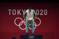 Akbar Djuraev of Uzbekistan bows as he arrives on the medals podium to receive his gold medal in men's 109kg weightlifting, at the 2020 Summer Olympics, Tuesday, Aug. 3, 2021, in Tokyo, Japan. (AP Photo/Seth Wenig)