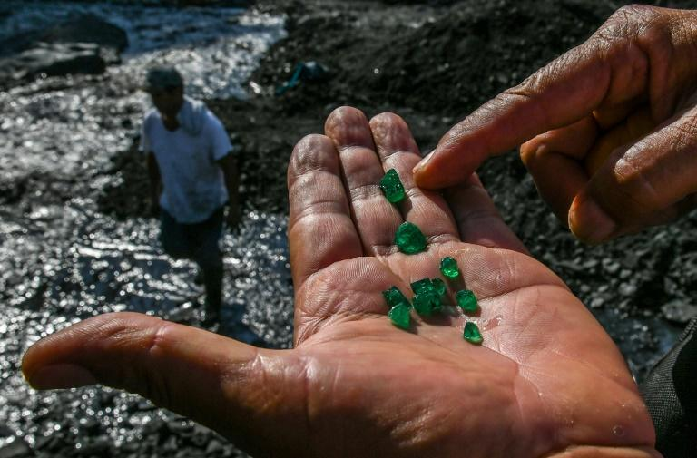 """An emerald seeker shows some of the green gems found in the Las Animas river close to a mine in Muzo, Colombia -- known as the """"emerald capital of the world"""""""