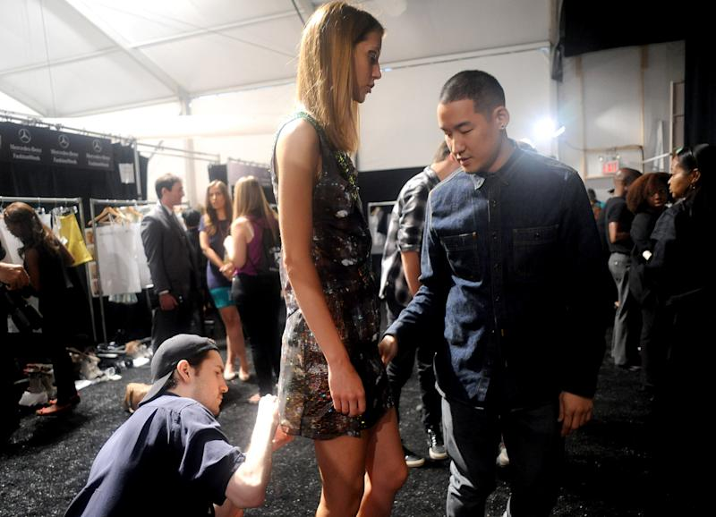 Designer Richard Chai, right, examines a dress before the Richard Chai Spring 2013 collection is shown at Fashion Week in New York, Thursday, Sept. 6, 2012.(Photo by Diane Bondareff/Invision/AP Images)