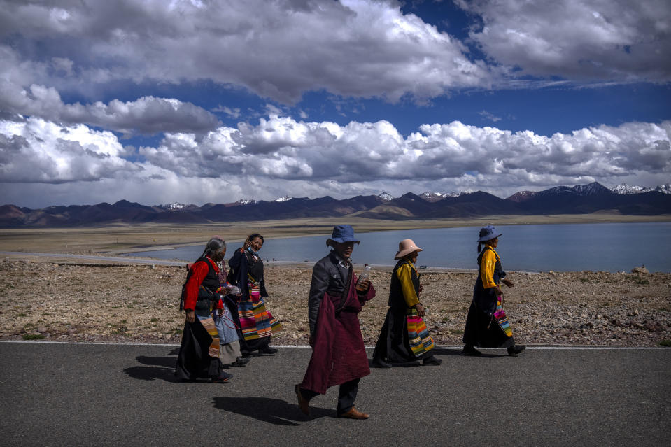 Members of the Buddhist faithful walk along a path to a holy site in Namtso in western China's Tibet Autonomous Region, Wednesday, June 2, 2021, as seen during a government organized visit for foreign journalists. High-pressure tactics employed by China's ruling Communist Party appear to be finding success in separating Tibetans from their traditional Buddhist culture and the influence of the Dalai Lama. (AP Photo/Mark Schiefelbein)