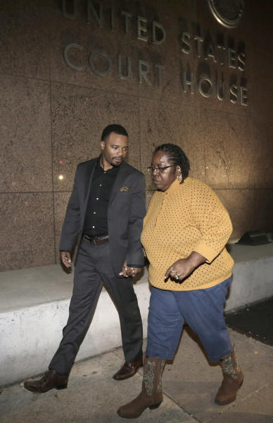 Gloria Corbin, right, mother of former NFL wide receiver Sam Hurd, is led by an unidentified family member from the federal court building after the sentencing of her son, in Dallas on Wednesday, Nov. 13, 2013. Hurd was sentenced to 15 years in prison for his role in starting a drug-distribution scheme while playing for the Chicago Bears, completing a steep downfall that ended his football career and left his future in tatters. (AP Photo/LM Otero)