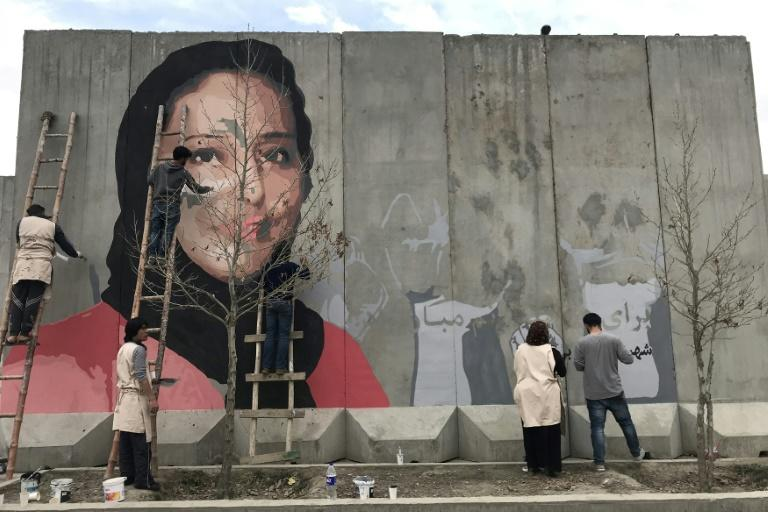 Artists paint a mural of Hamida Barmaki, who, along with her husband and children, was killed in a 2011 suicide attack, on a blast wall near the home of warlord Gulbuddin Hekmatyar, whose followers carried out the attack