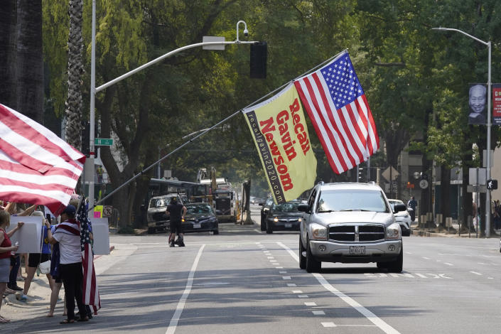 A flag calling for the recall of Gov. Gavin Newsom hangs in front of cars passing the Capitol during a demonstration against mandatory vaccinations in Sacramento, Calif., Monday, Aug. 16, 2021. California is mandating COVID-19 vaccinations for all health care workers and will require state government and school staff to be vaccinated or regularly tested. (AP Photo/Rich Pedroncelli)