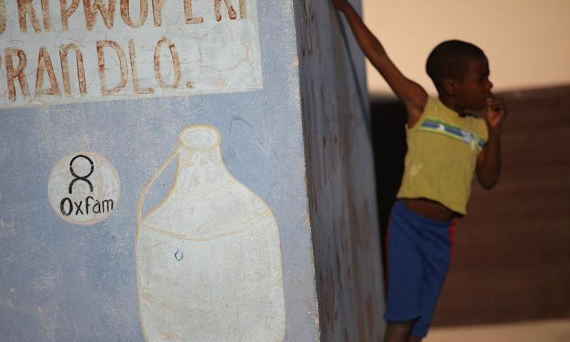 Haitian boy stands next to Oxfam sign