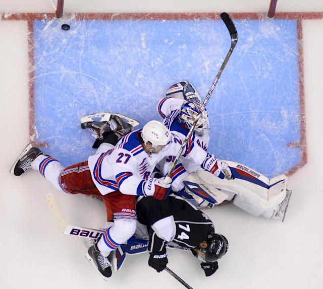 Los Angeles Kings left wing Dwight King, middle, scores between New York Rangers defenseman Ryan McDonagh, left, and goalie Henrik Lundqvist, of Sweden, during the third period of Game 2 in the NHL Stanley Cup Final hockey series in Los Angeles, Saturday, June 7, 2014
